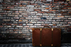 Old suitcase. Old vintage suitcase against a bricks wall Stock Photography