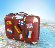 Old suitcase with air ticket and striples flags on blurred world Royalty Free Stock Image