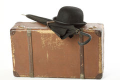 Old suitcase, bowler hat and umbrella Stock Image
