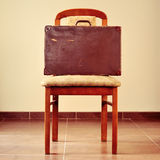 Old suitcase on a chair Royalty Free Stock Photo