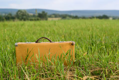Old suitcase in field royalty free stock image