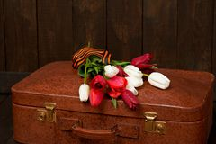 Old suitcase with flowers, symbol of victory in world war II with St. George`s ribbon, a dark wooden background, retro concept stock photo