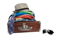 Old suitcase and  folded things on it and sunglasses near it Royalty Free Stock Photography