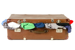 Old suitcase full with clothes before white background Royalty Free Stock Image