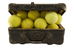 Old suitcase full of tennis balls. Old brown suitcase full of tennis balls isolated on white stock image