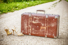 Old suitcase and high heel sandals on the rural road Stock Photography
