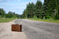 Old suitcase left on a dirt road Royalty Free Stock Image
