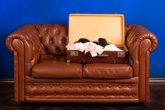 Old suitcase with lingerie on a ancient leather couch Royalty Free Stock Photo