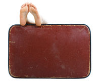 Old suitcase with naked female feet on top. Old brown suitcase with naked female feet resting on top - isolated on white Royalty Free Stock Images
