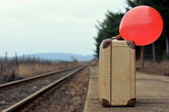 Old suitcase with a red balloon at the train station with retro effect Stock Images
