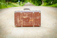 Old suitcase on the rural road Stock Photos