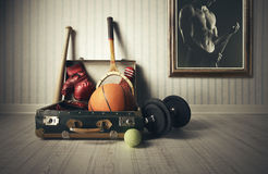 Sports equipment. Old Suitcase with sports equipment and athlete photo Stock Image