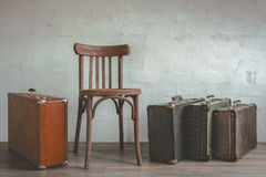 Old suitcase and a wooden chair Stock Image