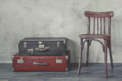 Old suitcase and a wooden chair Stock Photo