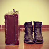Old suitcase and worn boots Stock Photos