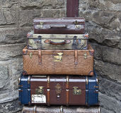 Old suitcases. / vintage luggage stacked against stone wall Stock Images