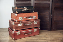 Old suitcases and dark wooden screen. Old suitcases on a background of dark wood screen Royalty Free Stock Photos