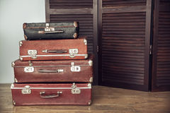 Old suitcases and dark wooden screen. Old suitcases on a background of dark wood screen Stock Photos