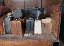 Old suitcases on an old wooden cart. Old suitcases, luggage, and boxes on an old wooden railway cart Royalty Free Stock Photos