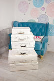 Old suitcases painted with white paint. A blue sofa in a modern Royalty Free Stock Photography