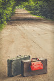 Old suitcases and red bag. Two old suitcases and red bag standing on the road Stock Photos