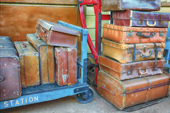 Old suitcases on trolleys in a station. Old suitcases stacked on trolleys in a station Royalty Free Stock Image
