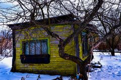 An old, summer yellow house stands in a winter garden. Surrounded by fruit trees and with garden tools nearby stock photo