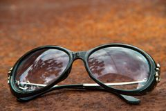 Old sunglasses in cloudy day on rusty metallic surface background stock photography
