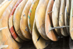 Old surf boards. Old used orange-colored surf boards stacked along each other at beach surf camp Royalty Free Stock Photos