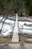 Old suspension bridge. Over a foaming stream Royalty Free Stock Image