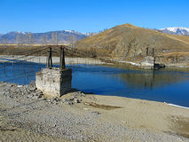 The old suspension bridge across mountain river. The old rope suspension bridge over the river Katun in the Altai Mountains. Demolished, remained as a legacy of Stock Image