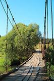 Old suspension bridge across the river. Stock Image