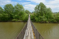 Old suspension bridge across the river. On a summer sunny day Royalty Free Stock Images