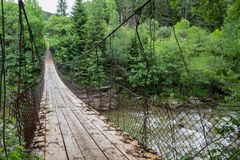 Old suspension bridge over the river in the forest royalty free stock images