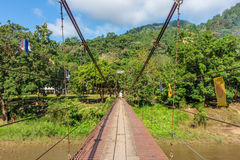 Old suspension iron bridge across river Royalty Free Stock Photo