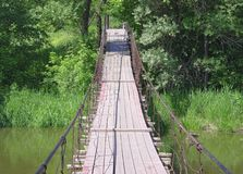 Old suspension walk bridge across river in forest Stock Photo