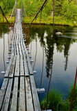 Old suspension walk bridge across river in the forest Royalty Free Stock Photo