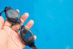 Old Swimming goggles more Scratch on glass in hand. Royalty Free Stock Photo