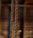 Old swing rope in barn. Old swing rope hanging in rustic barn Royalty Free Stock Photos
