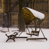 Old swing under the snow. In the yard in brown tones Royalty Free Stock Photos