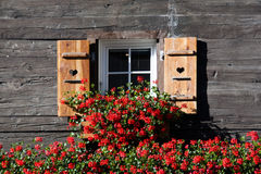 Old swiss cottage window. Decorated with red flowers Stock Photography