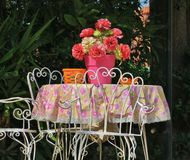 Old table in the middle of the courtyard with pink flowers royalty free stock photo