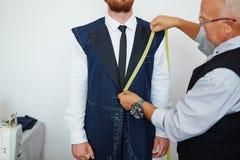 Old Tailor Measuring Model in Atelier Studio Stock Photo