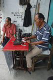 Old tailor. Old men tailor with glasses work in outdoor Royalty Free Stock Image