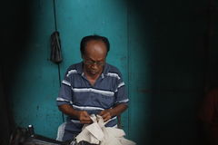 Old tailor. Old men tailor with glasses work in outdoor Stock Images
