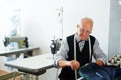Old Tailor Sewing Garments in Studio. Portrait of old man working in tailoring studio making clothes and hand stitching cloth Stock Photos