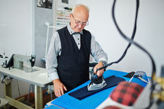 Old Tailor Working in Small Atelier Studio Stock Photography