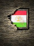 Old Tajikistan flag in brick wall. 3d rendering of a Tajikistan flag over a rusty metallic plate embedded on an old brick wall Stock Photography