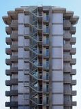 An old tall concrete apartment block with repeating concrete balconies and external fire escape stairs with metal railings against. A blue sky stock image