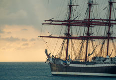 Old tall ship. Old sailing ship against sunset. Ancient sailboat on a stormy sky background. Historic three-masted sailing ship. Nautical landscape - sea voyage Royalty Free Stock Photography